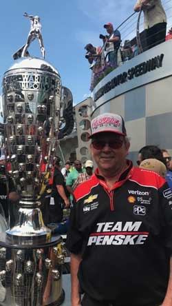 Team Penske's David Little next to the Borg Warner Trophy at the Indianapolis 500