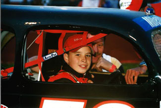 A young Coleman Pressley enjoys the best seat in the house inside his dad's race car.